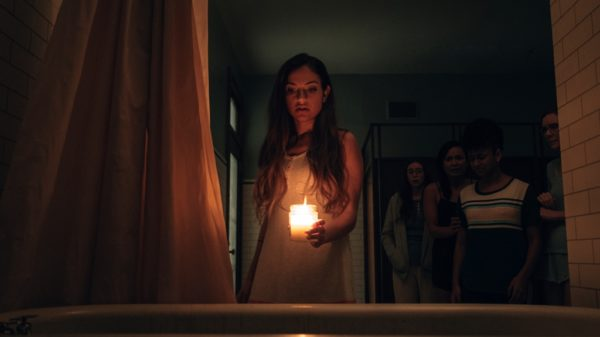 Girl stands in the dark with a candle in 'Seance'