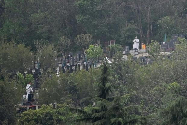 People wearing protective suits are seen in the  Biandanshan cemetery in Wuhan. For many their first...