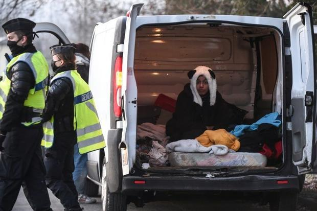 A raver wearing a panda hat sits in a van after being questioned by French police following the brea...