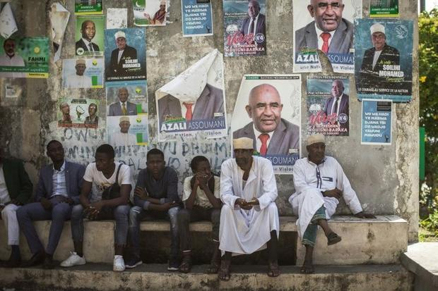 Supporters of the opposition Juwa Party sit beneath campaign posters  waiting for a rally in a villa...