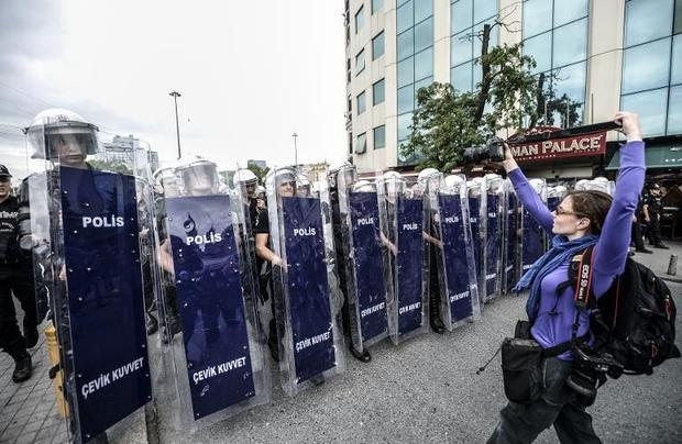 A photographer takes a photo of Turkish riot police officers standing in line as they block access t...