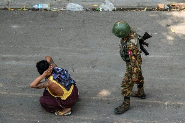 A soldier stands next to a detained man during a demonstration against the military coup in Mandalay...