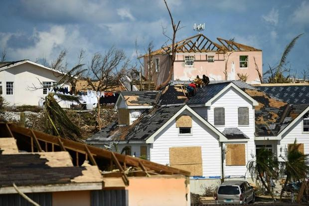 While some were fleeing the island  these residents were repairing a roof in the devastated neighbor...