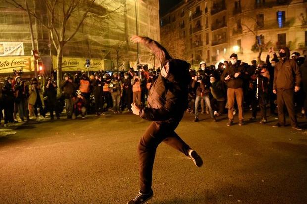 A protester throws a stone at police officers during a demonstration against the imprisonment of Spa...