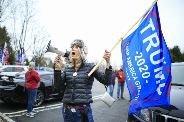 """A woman shouts slogans as Trump Supporters gather during a car rally under the slogan """"Stop the St..."""