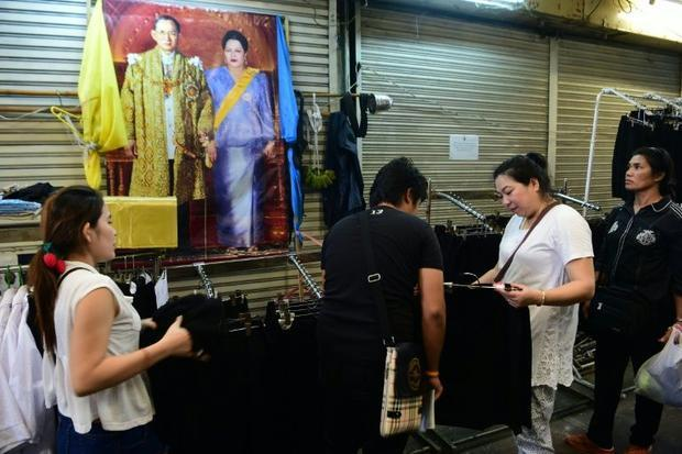 Mourners buy black clothing in a shop next to photos of the late Thai King Bhumibol Adulyadej in Ban...