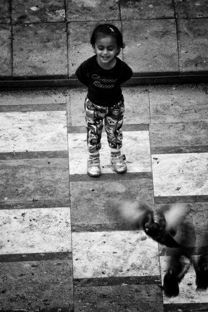A girl chasing pigeons in Mumbai  India.