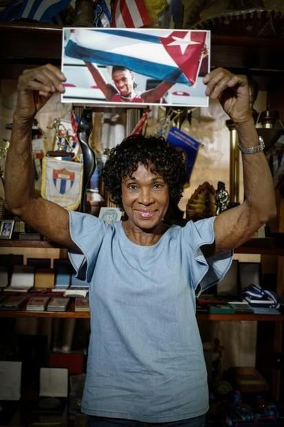Cuban former track and field athlete Ana Fidelia Quiros poses with a picture of herself holding the ...