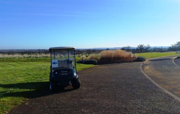 A golf cart sits waiting early in the morning  ready for the first golfers to arrive.
