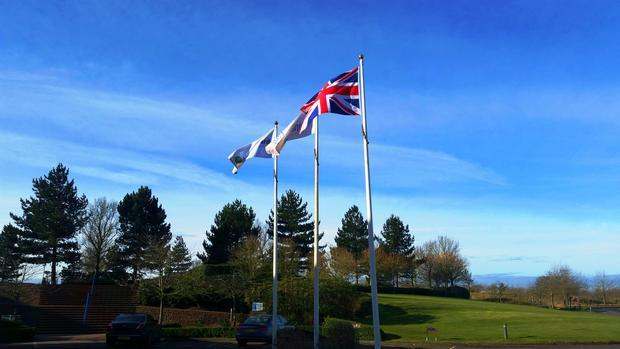 The front of the hotel  with the union flag fluttering alongside golf related flags.