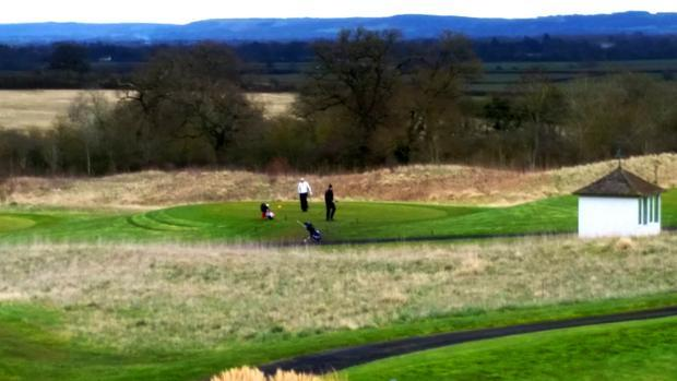 Long shot of some golfers struggling to make the vital put.
