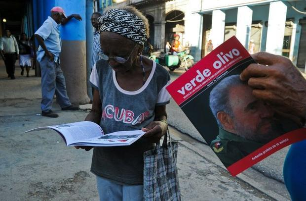 Cubans read issues of Verde Olivo magazine with a front page displaying a photo of their former lead...