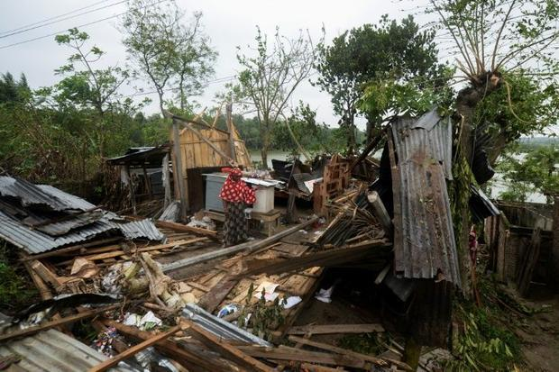 A woman looks at what is left of her home after Cyclone Amphan hit Satkhira district in Bangladesh