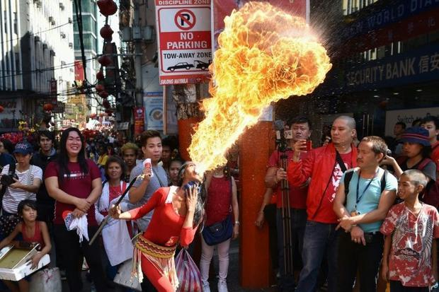 A fire breather performs during celebrations for the Lunar New Year of the Pig in Manila's Chin...