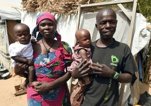 Bitrus Yakubu and his wife Maryam  an internally displaced couple  stand beside their tent holding t...