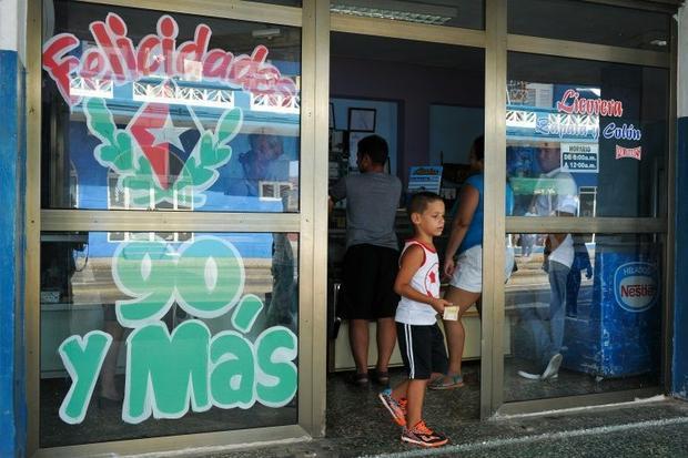 A boy walks next to an inscription on a window about Cuban former president Fidel Castro  in Havana ...
