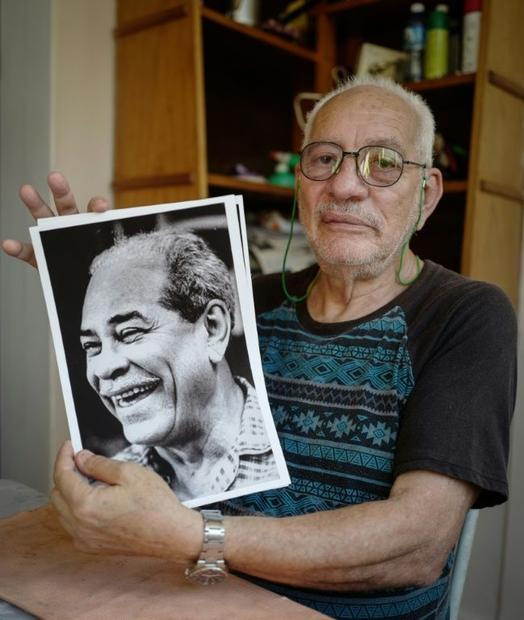 Dissident Vladimiro Roca poses with a picture of his father Blas Roca  one of the founders of the Cu...