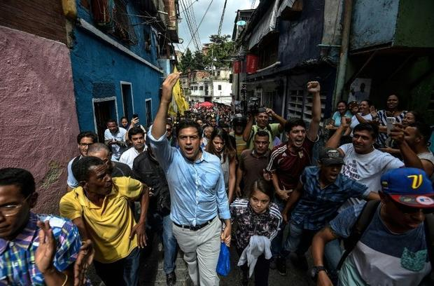 The opposition's candidate for governor for the state of Miranda  Carlos Ocariz (C)  greets sup...