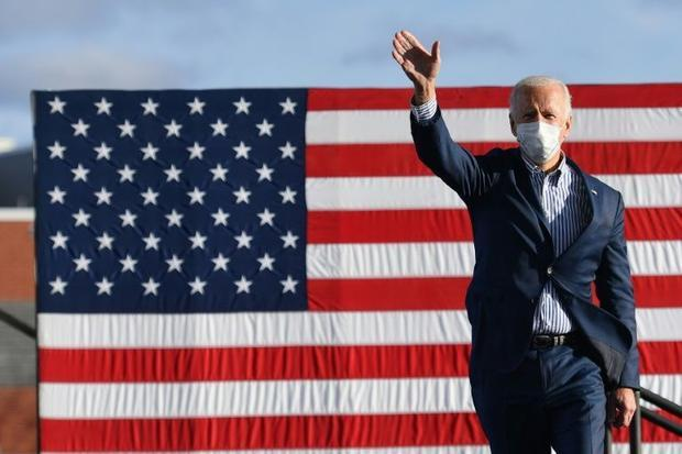 Democratic presidential nominee Joe Biden waves to supporters before speaking at a drive-in rally in...