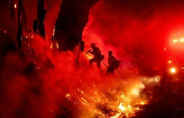 Firefighters try to control one of the fires in  California this month.Such blazes are intensifying ...