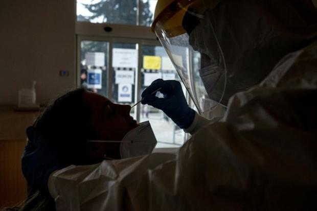 A Czech soldier wearing protective equipment (PPE) takes a sample from a patient at a coronavirus te...
