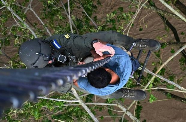 A man who got trapped in a flood and was clinging to a tree is rescued by members of the Honduran Ai...