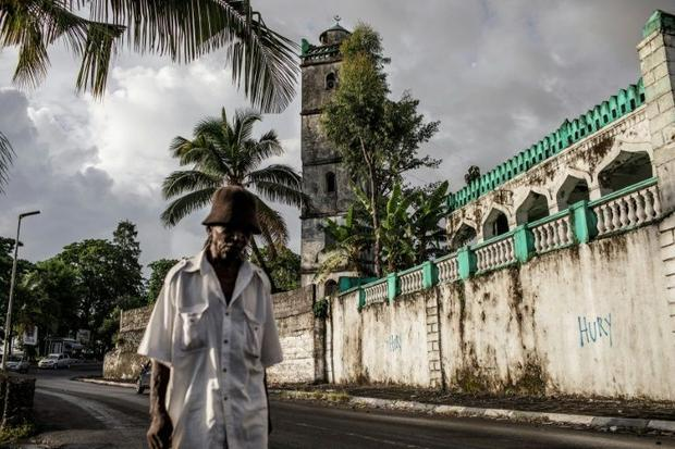 An elderly resident walks past a mosque in downtown Moroni. The grind of poverty in the Comoros can ...
