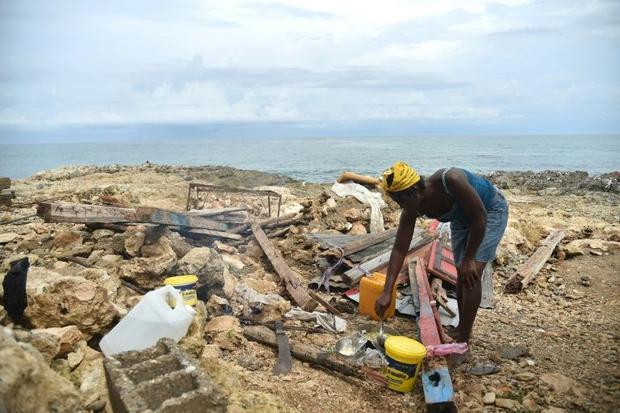 Leolien prepares food next what remains of her house destroyed by Hurricane Matthew in the neighborh...