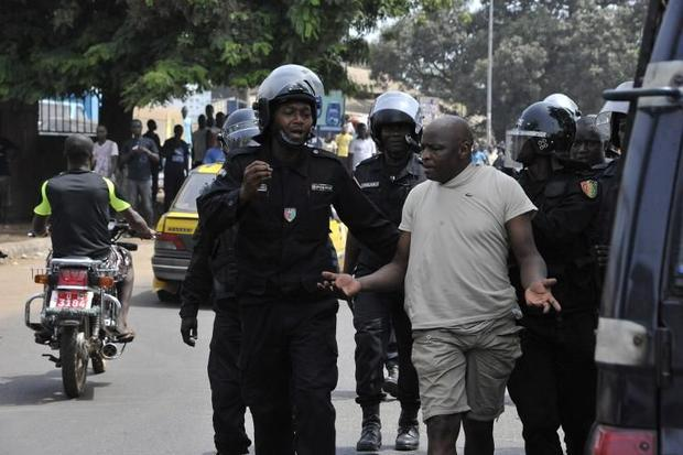 Police make an arrest on April 23 in Conakry during a protest called by the opposition against a dis...