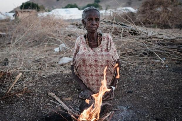 Ethiopian Arrafu Mbaye  70-year-old who fled the Tigray conflict  burns wood to cook at the Um Raqub...