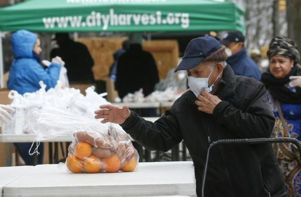 A man receives bags with food from City Harvest food bank