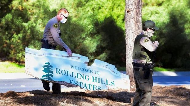 Police carry a sign broken in Woods' crash