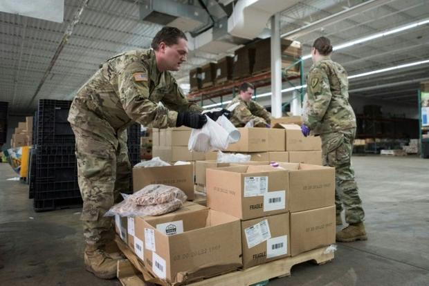 National Guard soldiers prepare packages of food in Indiana