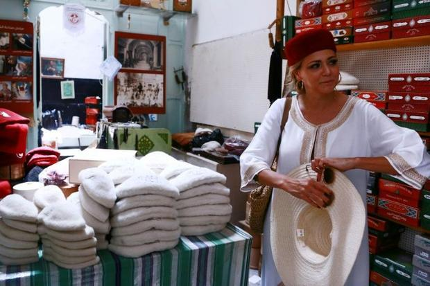 A tourist tries on a traditional Tunisian hat in a Tunis bazaar on June 28  2019
