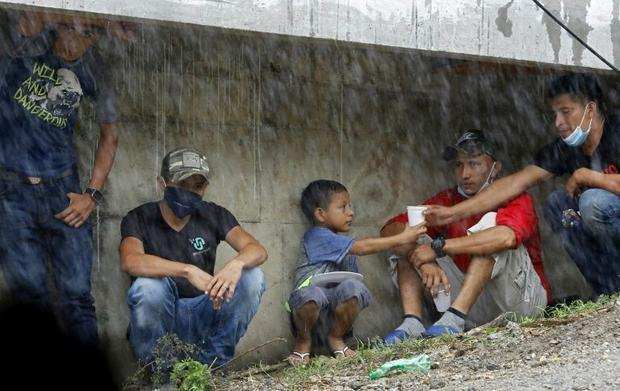 People take refuge under La Democracia bridge while waiting for relatives to be rescued from floods ...