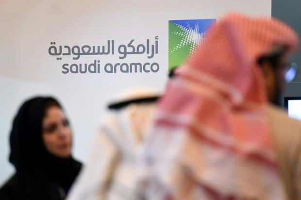 This file picture taken on January 25  2016  shows investors standing in front of the logo of Saudi ...