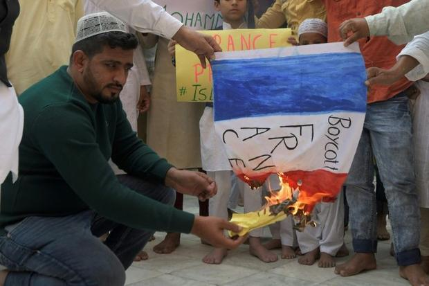 Muslim devotees burn a French national flag during a demonstration to protest against French Preside...