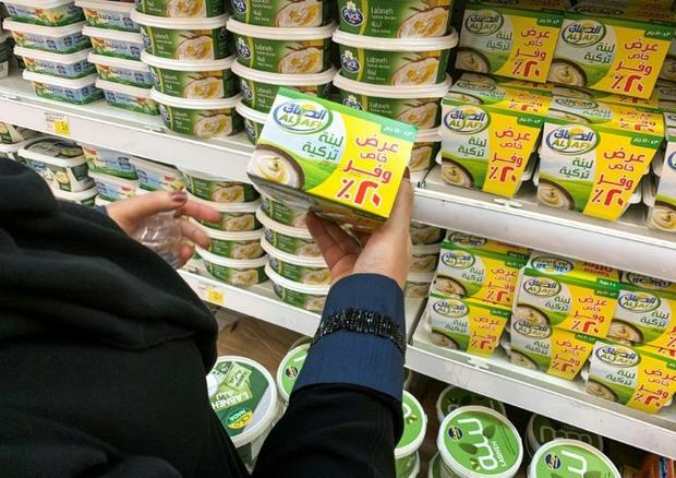 A woman holds a pack of Turkish labneh (strained yogurt) while shopping at a supermarket in Riyadh o...