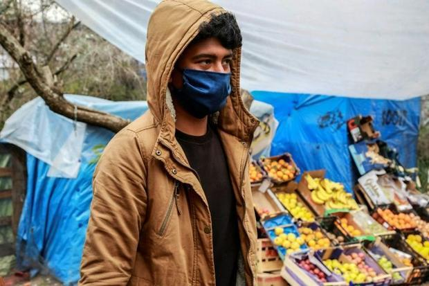 A migrant wearing a facemask walks by a fruit and vegetable stall at the Moria camp