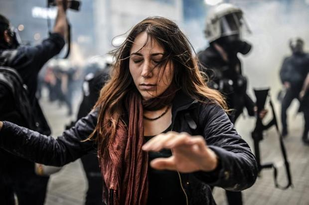 A protester walks away with closed eyes as Turkish riot police officers fire tear gas to disperse de...