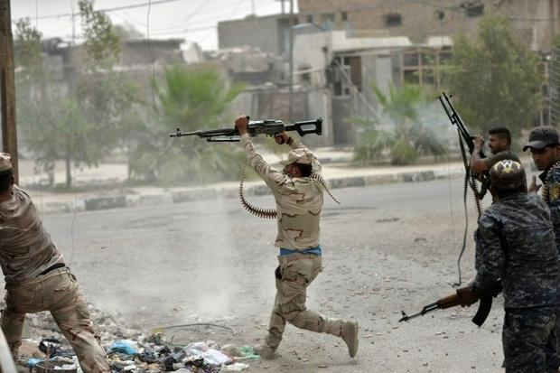 Iraqi government forces clash with Islamic State (IS) fighters in Fallujah on June 18  2016 as they ...