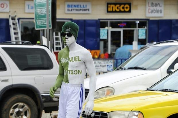 In Liberia  body painters earn their living by standing for hours in sweltering heat and traffic jam...