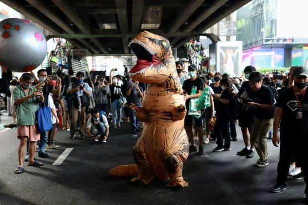 One dinosaur faces a threat from an 'asteroid' at the rally in Bangkok