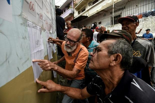 People look for their names on an electoral roll during regional elections in Caracas' municipa...