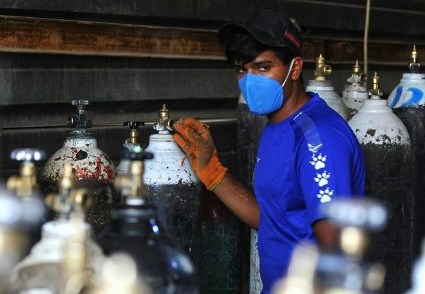 A worker refills oxygen cylinders at a factory in Taji district north of Iraq's capital Baghdad...