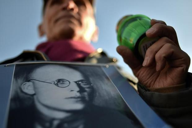 A man holds his father's portrait near the memorial to the victims of Soviet-era political repr...