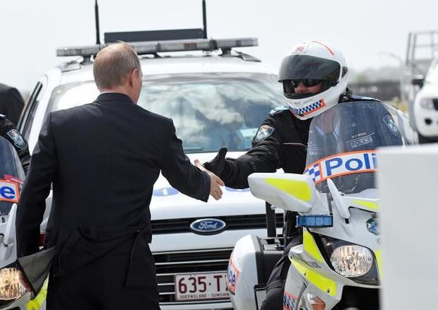 Russian President Vladimir Putin (L) shakes hands with members of his motorcycle escort at the airpo...