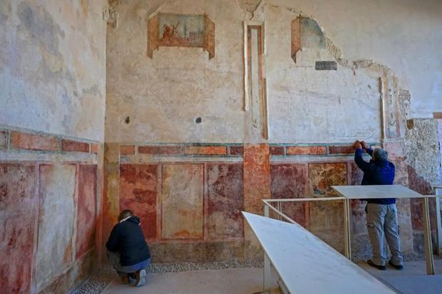 Specialists from the Israel Antiquities Authority restore an ancient wall painting in Herod's p...