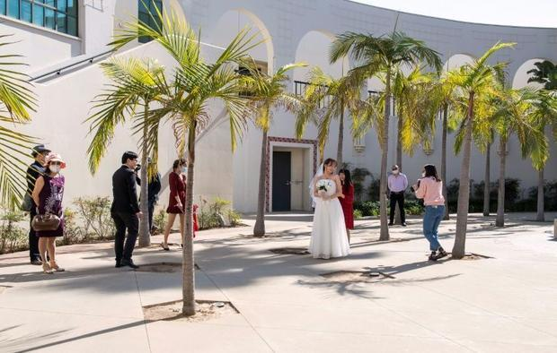 Facemasks and social distancing will forever be on this couple's wedding photographs to mark th...