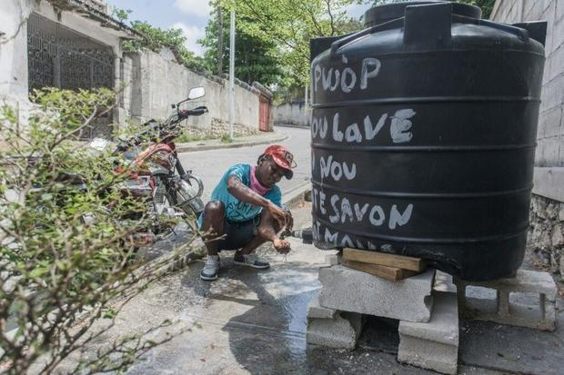 A motorcycle taxi driver washes his hands at one of the many hand washing kiosks set up in Port-au-P...